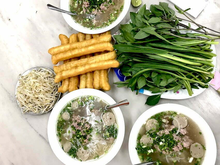 table with authentic pho noodle soup in ho chi minh