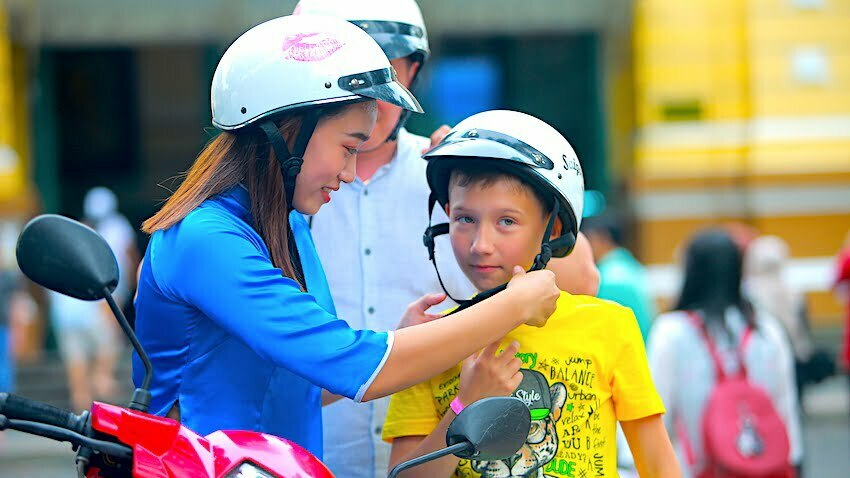 a female driver of motorbike food tour is wearing hemet for a young traveler